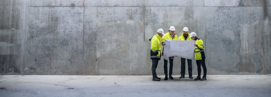Group of engineers standing in front of a concrete wall at a building site