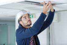 man looking into the panel of a ceiling