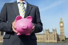 smart man in suit outside parliament holding pink piggy bank